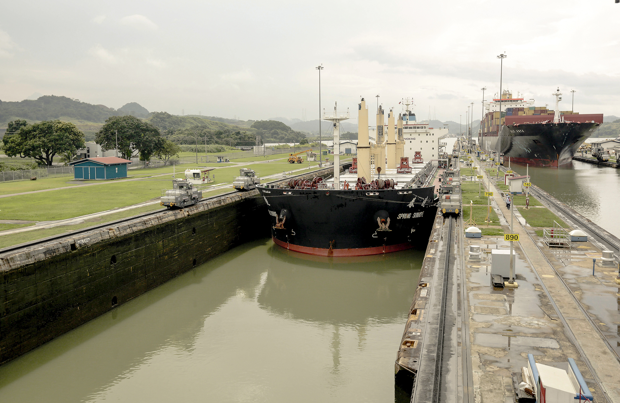 UNLOCKED: Two cargo ships navigate the Miraflores locks on the Panama Canal in Panama City. Post-Panamax ships will nearly triple the cargo capacity of ships currently able to pass through the canal. (AP Photo/Arnulfo Franco)
