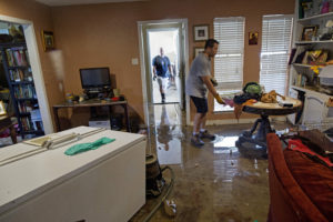 Raymond Lieteau pulls furniture out of his flood damaged home with the help of his friend Danny Lemoine, 48, in Baton Rouge. Lieteau had more than five feet of water in his home. (AP Photo/Max Becherer)
